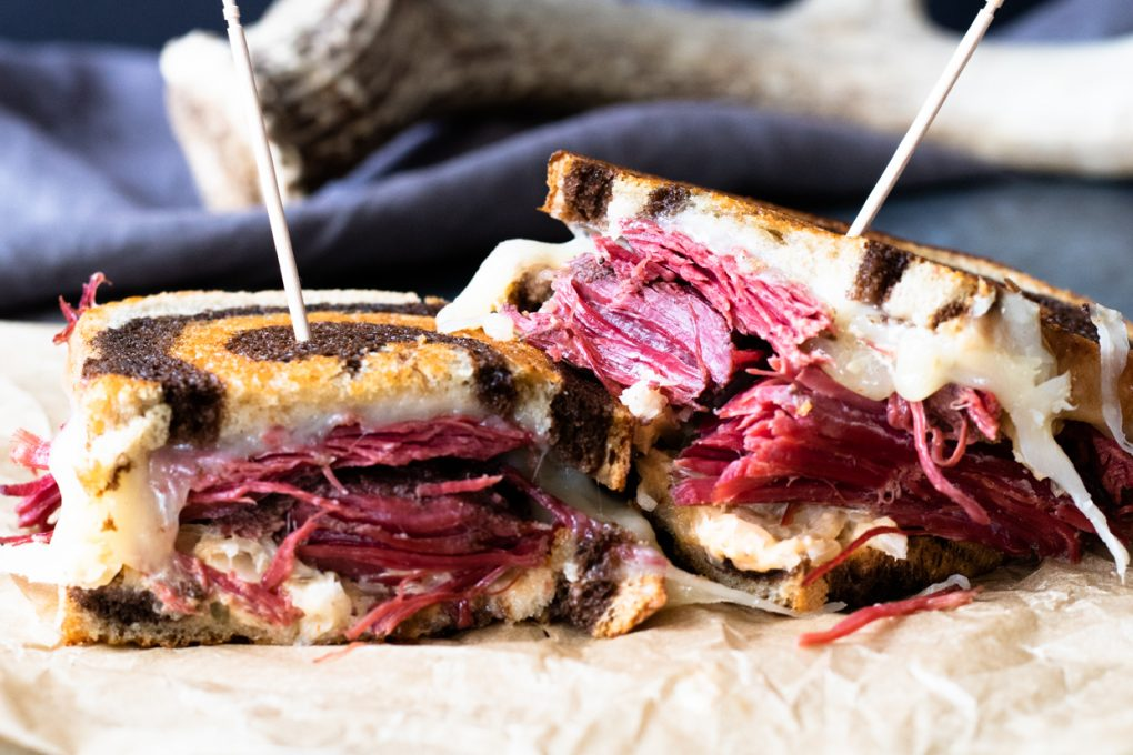 A hearty venison reuben sandwich made with a corned venison roast, sauerkraut, dressing, swiss cheese, and rye bread.