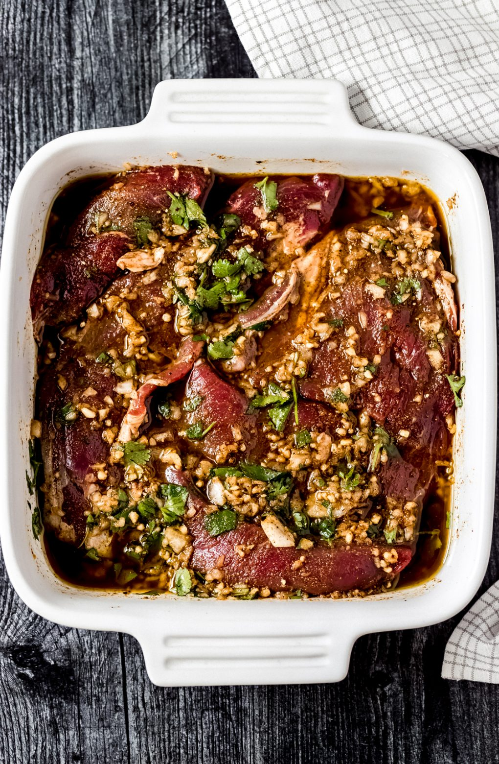 elk flank steak marinading in a white dish