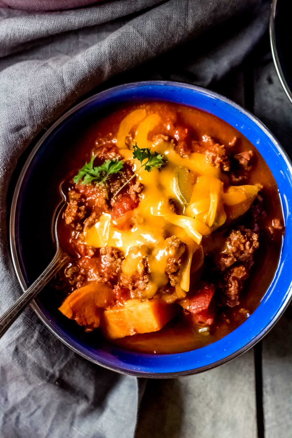 a bowl of elk chili with shredded cheddar cheese on top