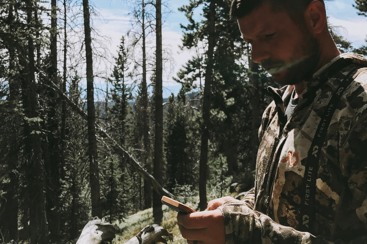 A man looking at gps during a colorado elk hunt wearing First Lite hunting apparel