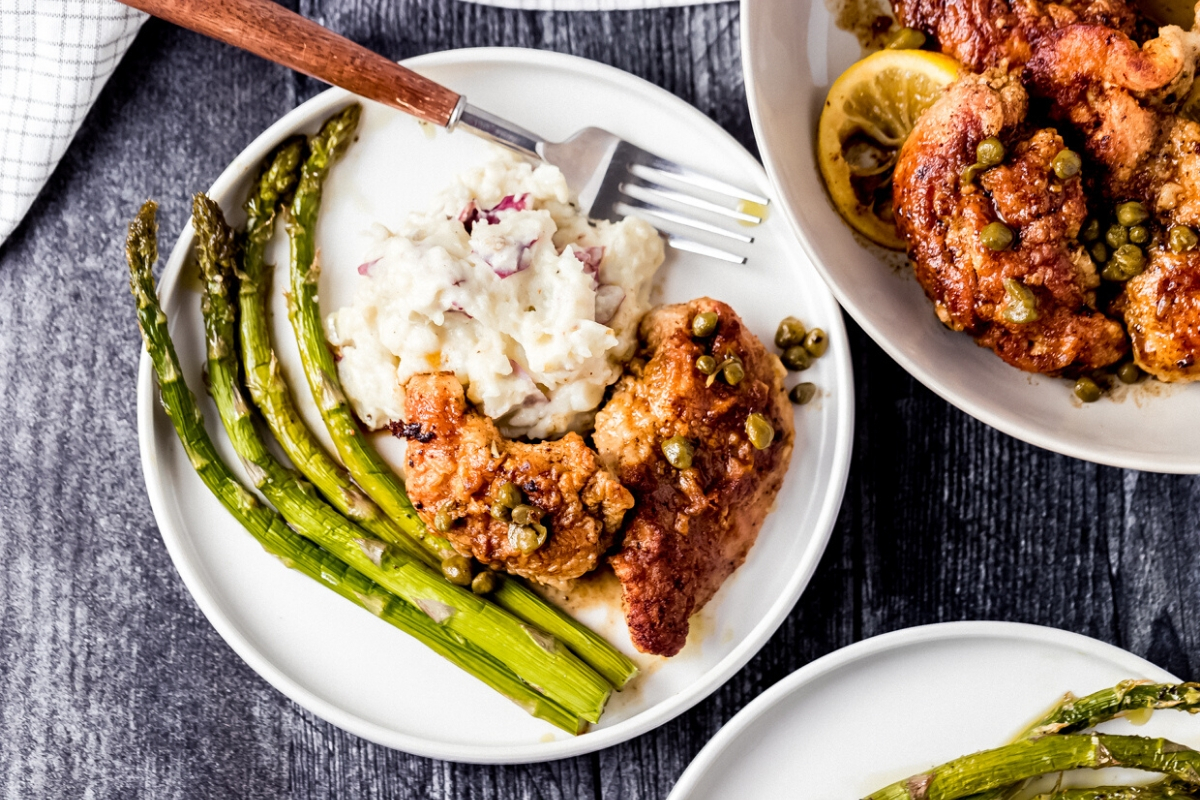 a plate of pheasant piccata, mashed potatoes, and asparagus