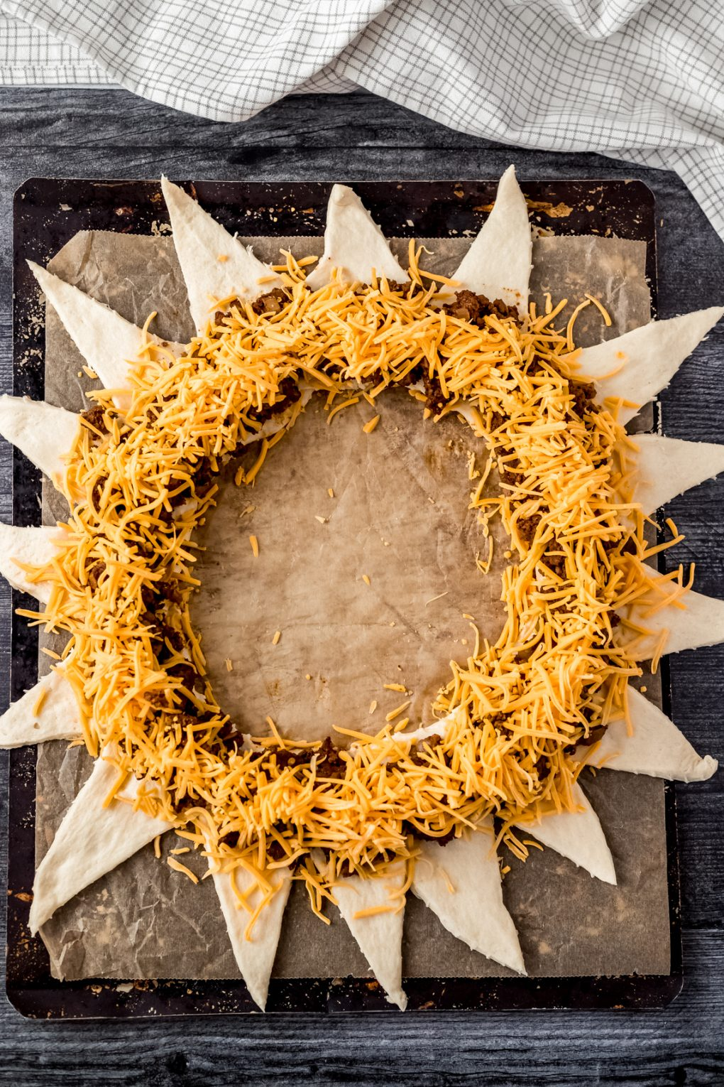 a circle of uncooked crescent rolls filled with ground venison taco meat and shredded cheddar