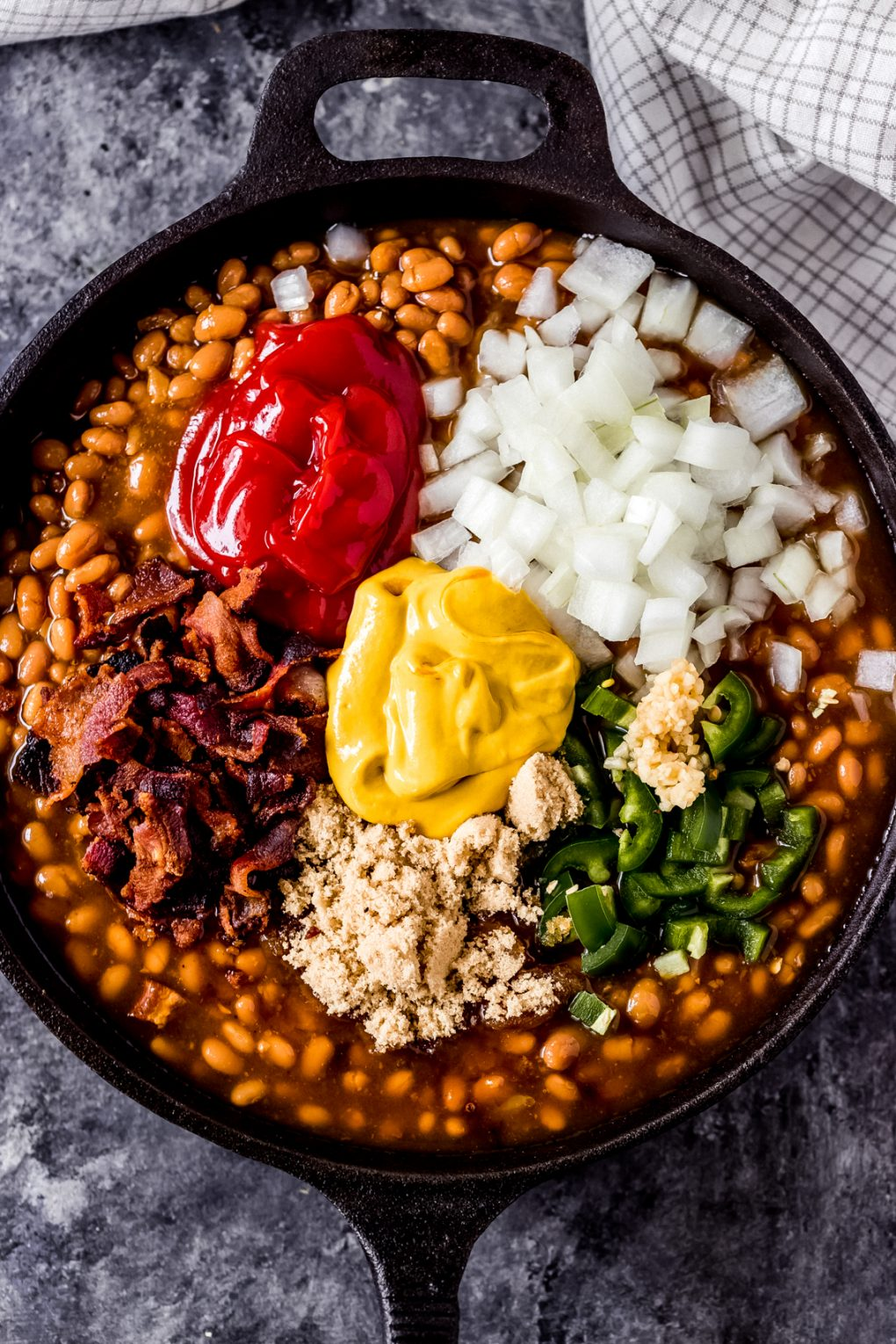 ingredients for smoked baked beans in a cast iron skillet