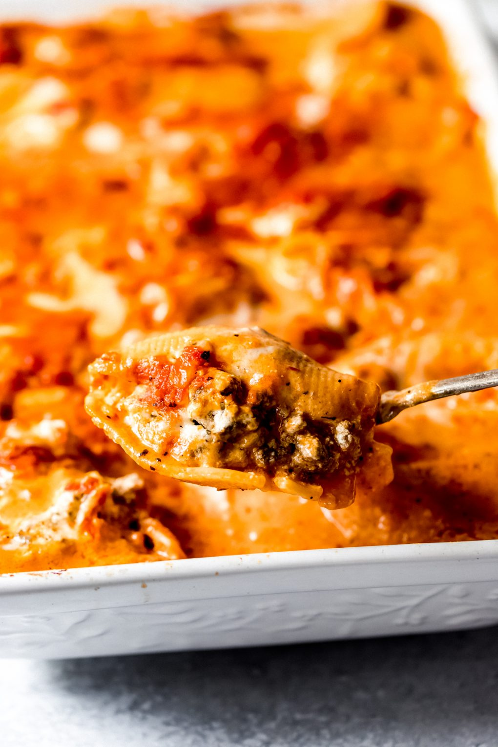 a person spooning out one venison stuffed shell
