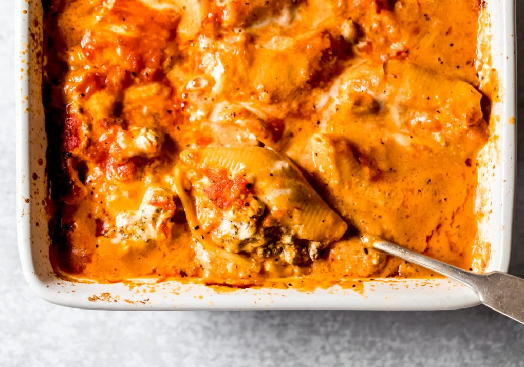 venison stuffed shells in a baking dish with a spoon