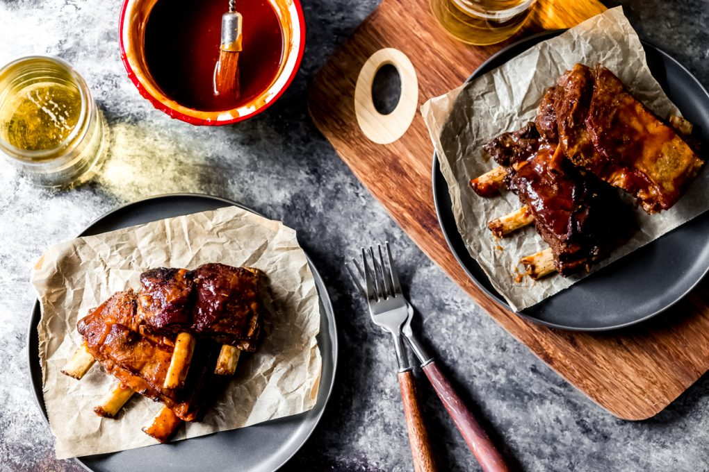 a table scene with plates of beer-braised bbq elk short ribs
