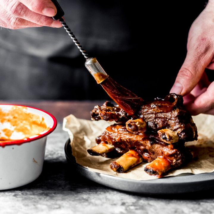 a man slathering BBQ sauce onto elk short ribs
