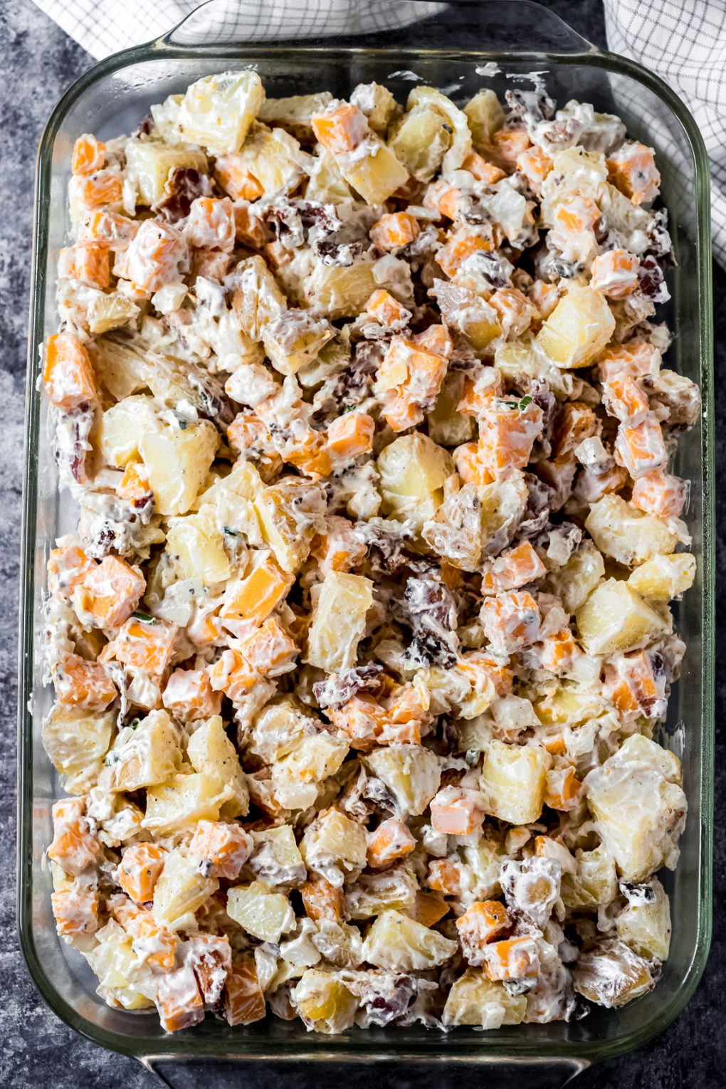 an unbaked dish of cheesy smoked potatoes