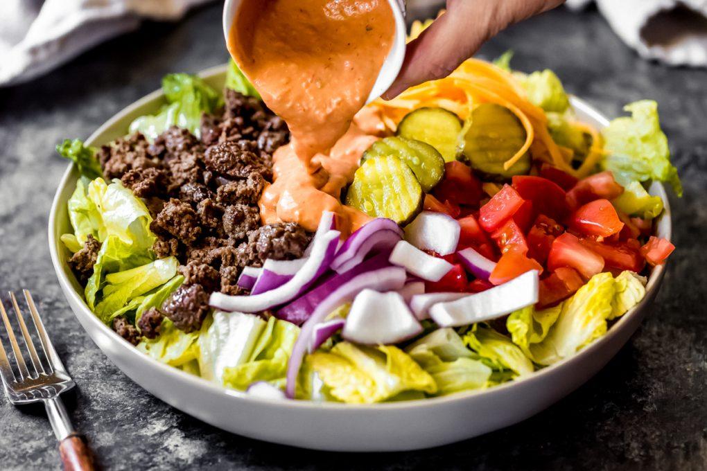 someone pouring thousand island dressing over a ground venison Big Mac salad