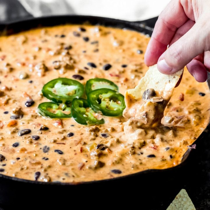a woman dipping a tortilla chip into loaded venison queso dip