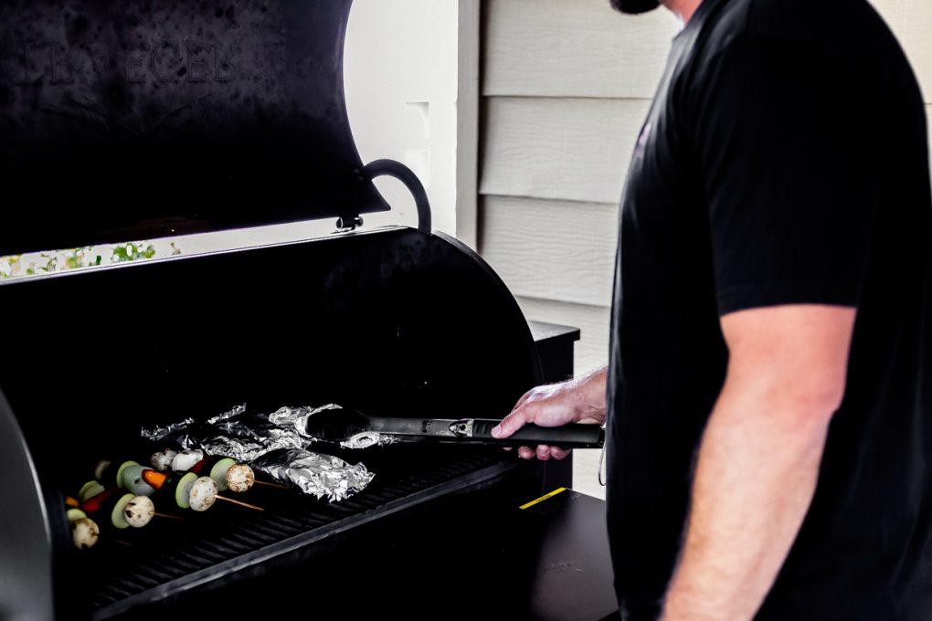 a man grilling elk sirloin foil packs