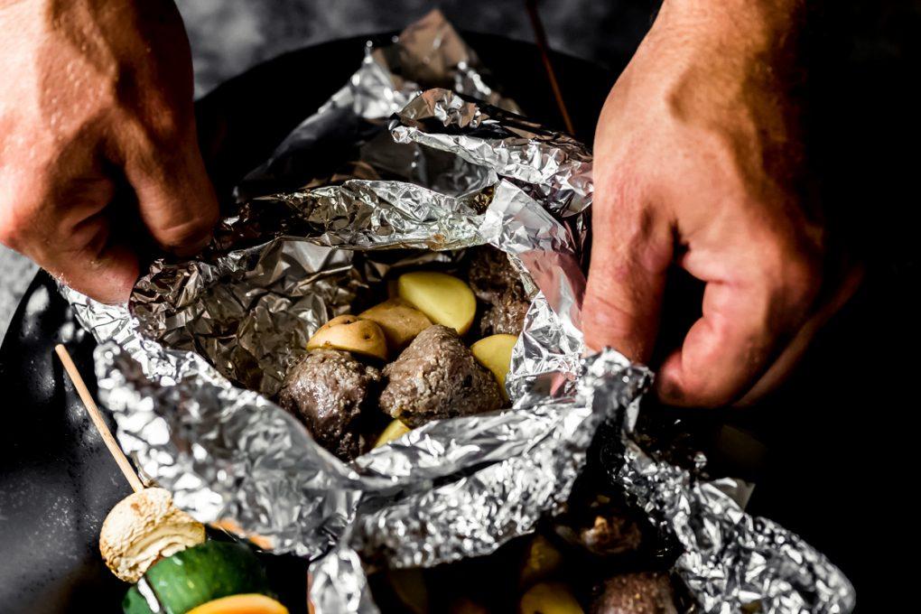 a man opening up an elk sirloin foil pack after cooking