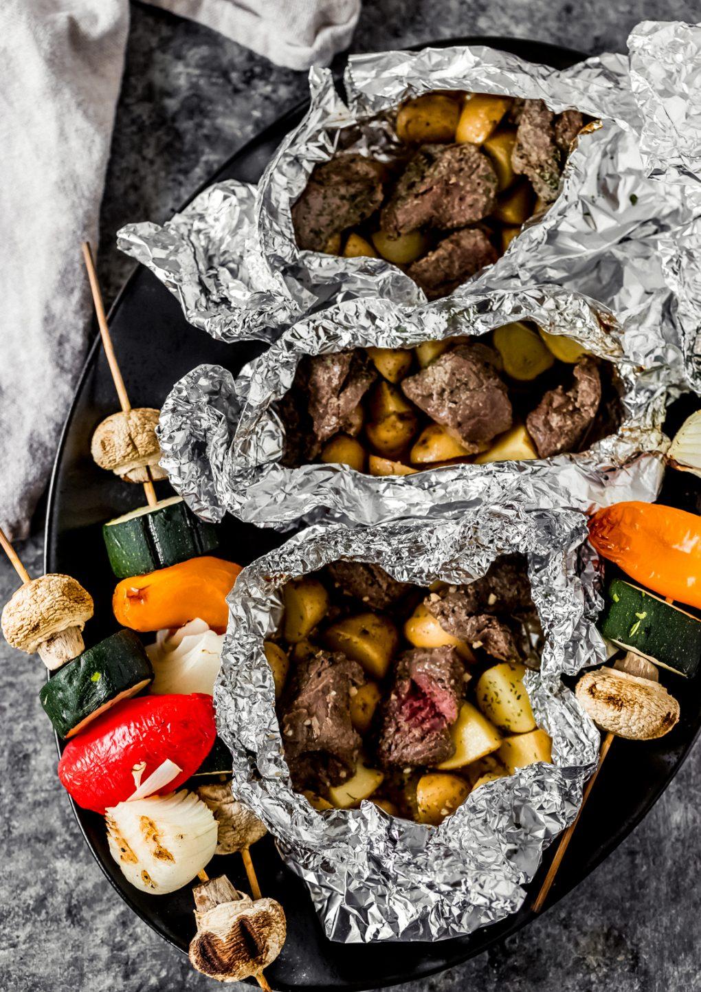 three elk sirloin steak and potato foil packs on a serving platter