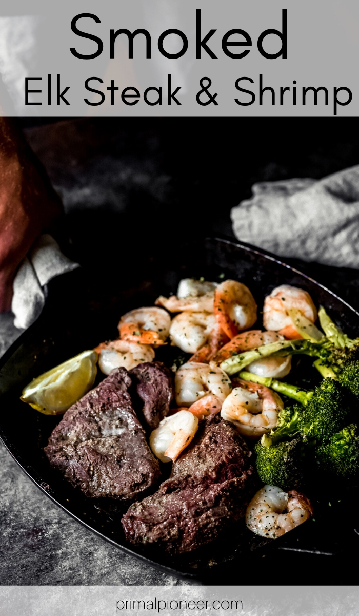 a man setting down a cast-iron skillet with smoked elk steak and shrimp