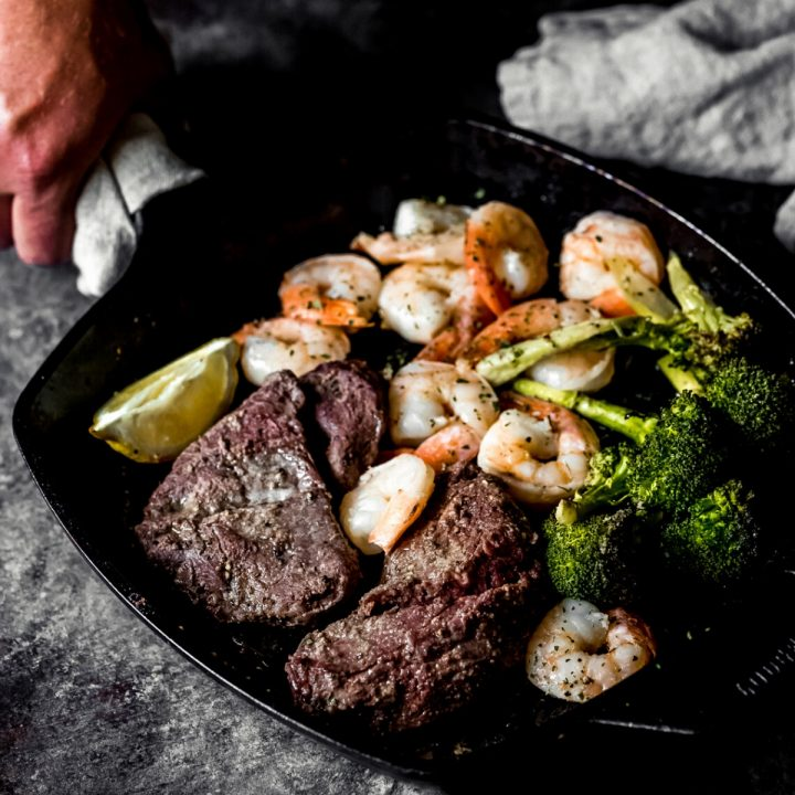 a man setting down a cast iron skillet with smoked elk steak and shrimp