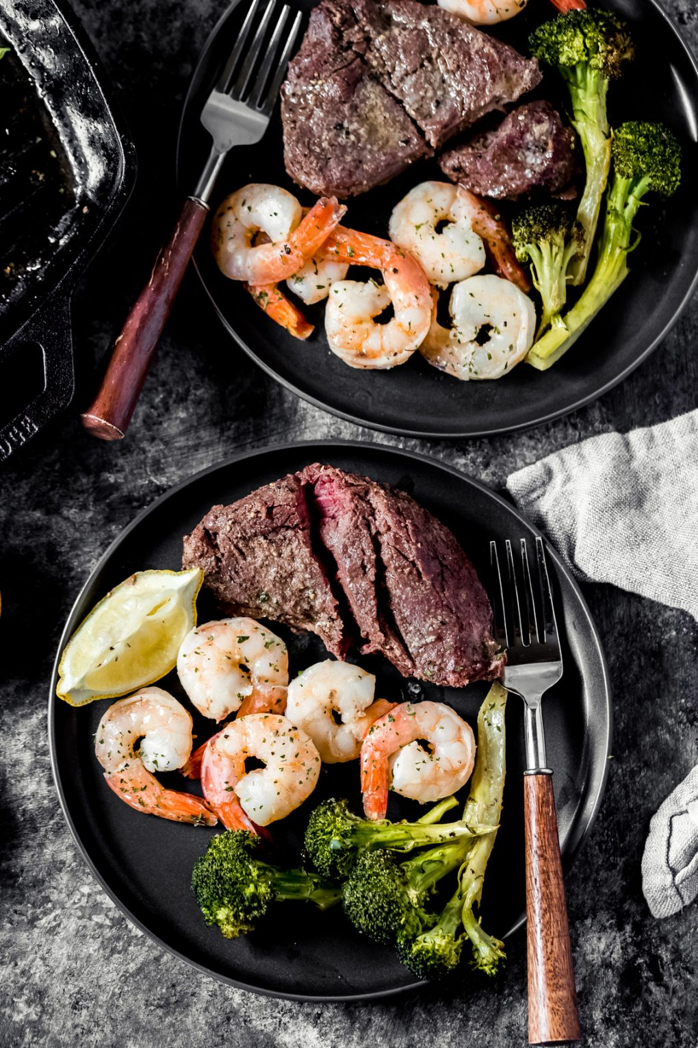 two plates of smoked elk steak and shrimp with broccoli