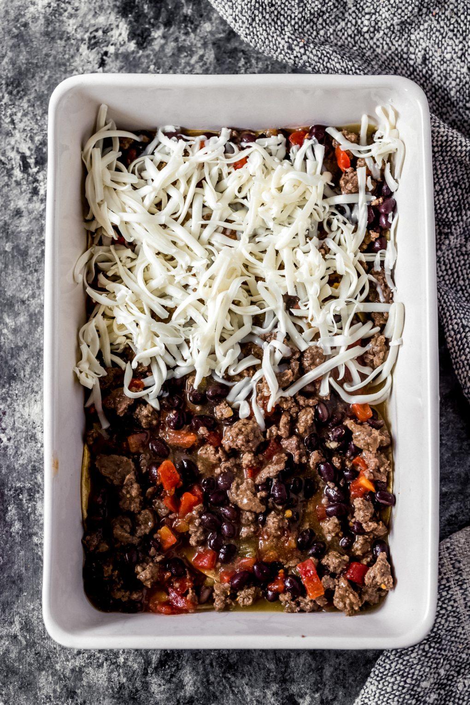 assembling ground venison green chile enchilada casserole in a baking dish