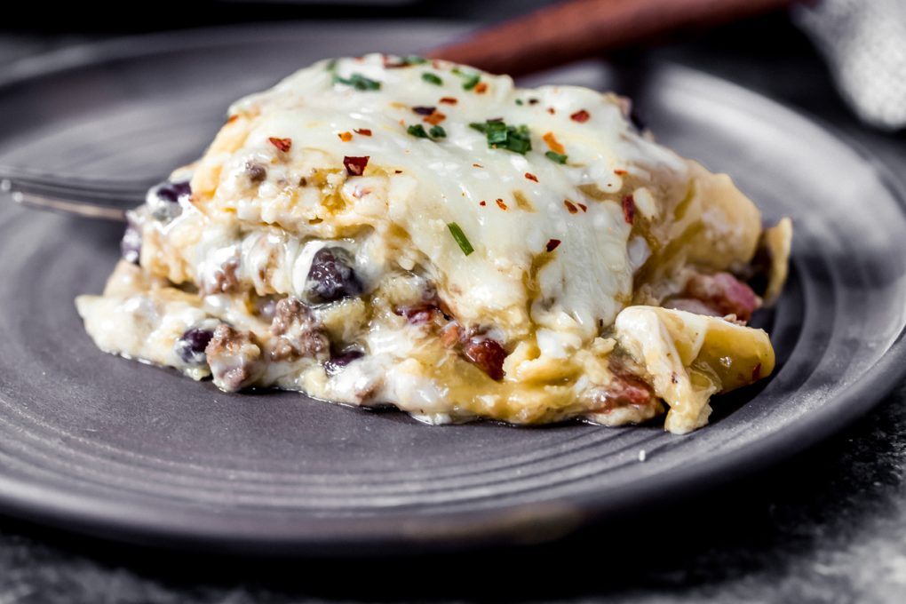 a serving of venison green chile enchilada casserole on a plate