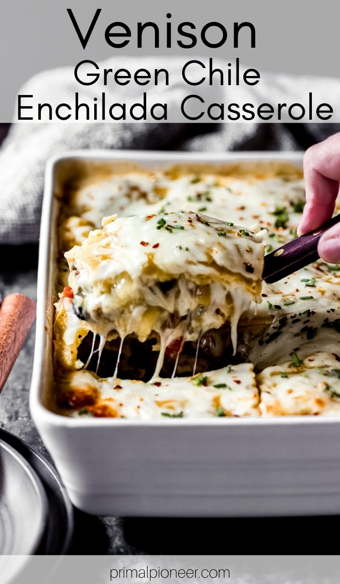 a person pulling up a serving of ground venison green enchilada casserole from a dish