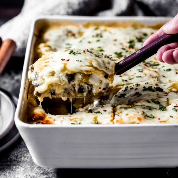 a woman pulling out a serving of ground venison green chile enchilada casserole