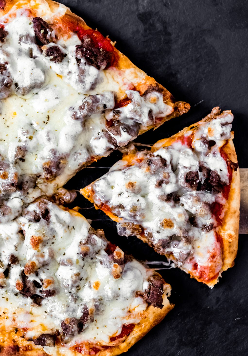 a venison pizza with one slice cut out