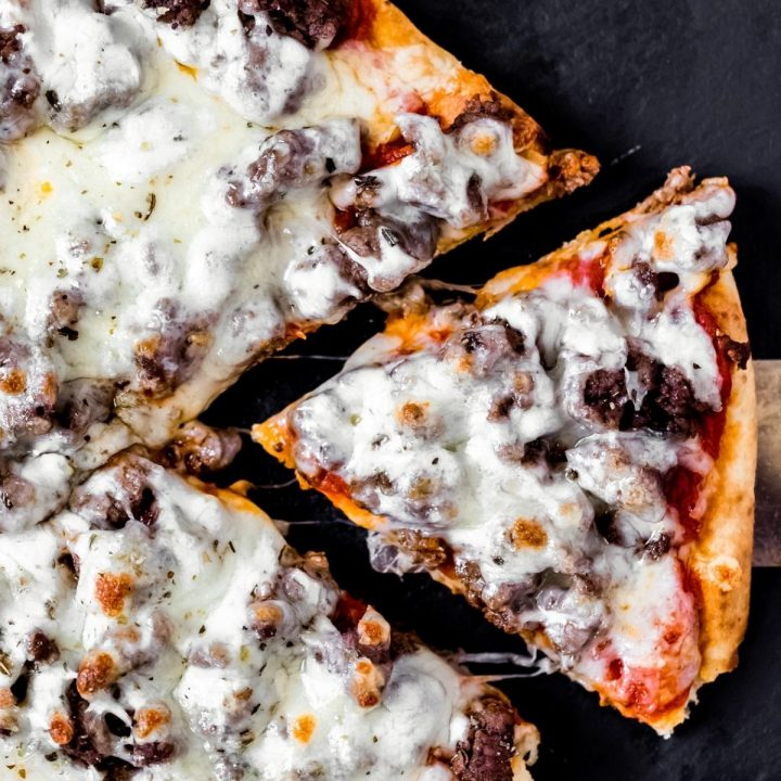 a venison pizza with a slice cut out of it