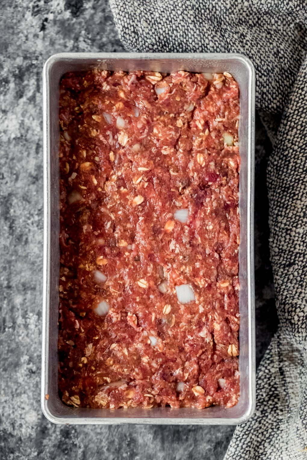 an uncooked venison meatloaf in a loaf pan