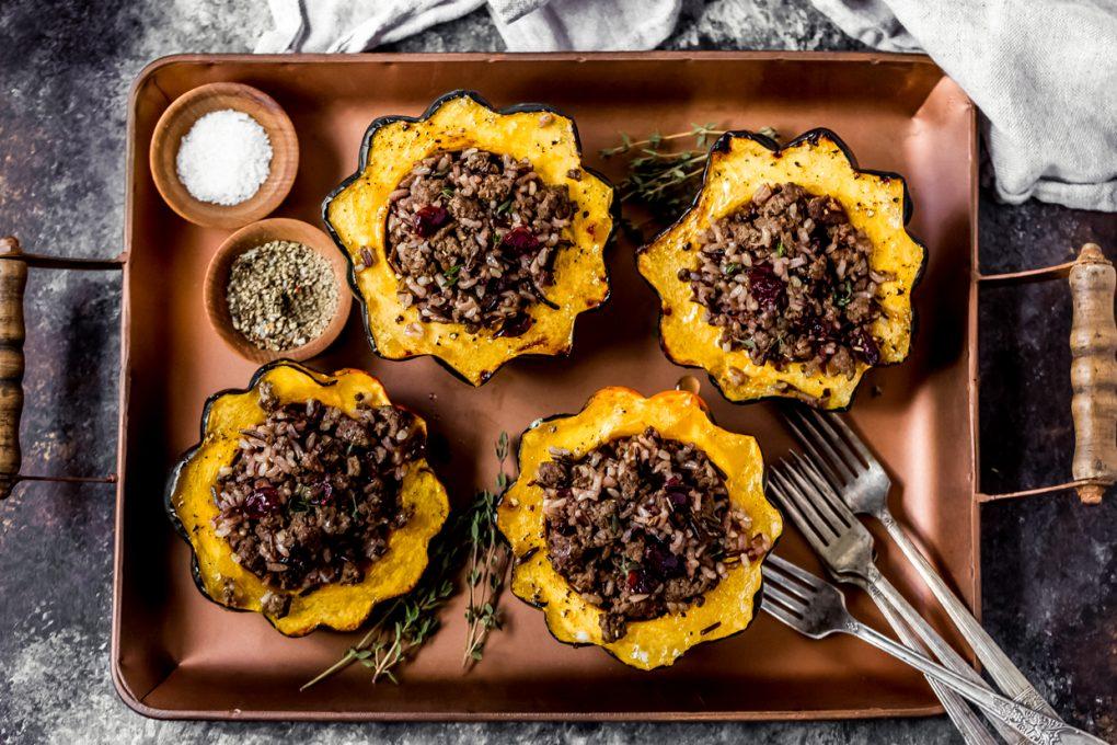 ground elk stuffed acorn squash on a serving platter