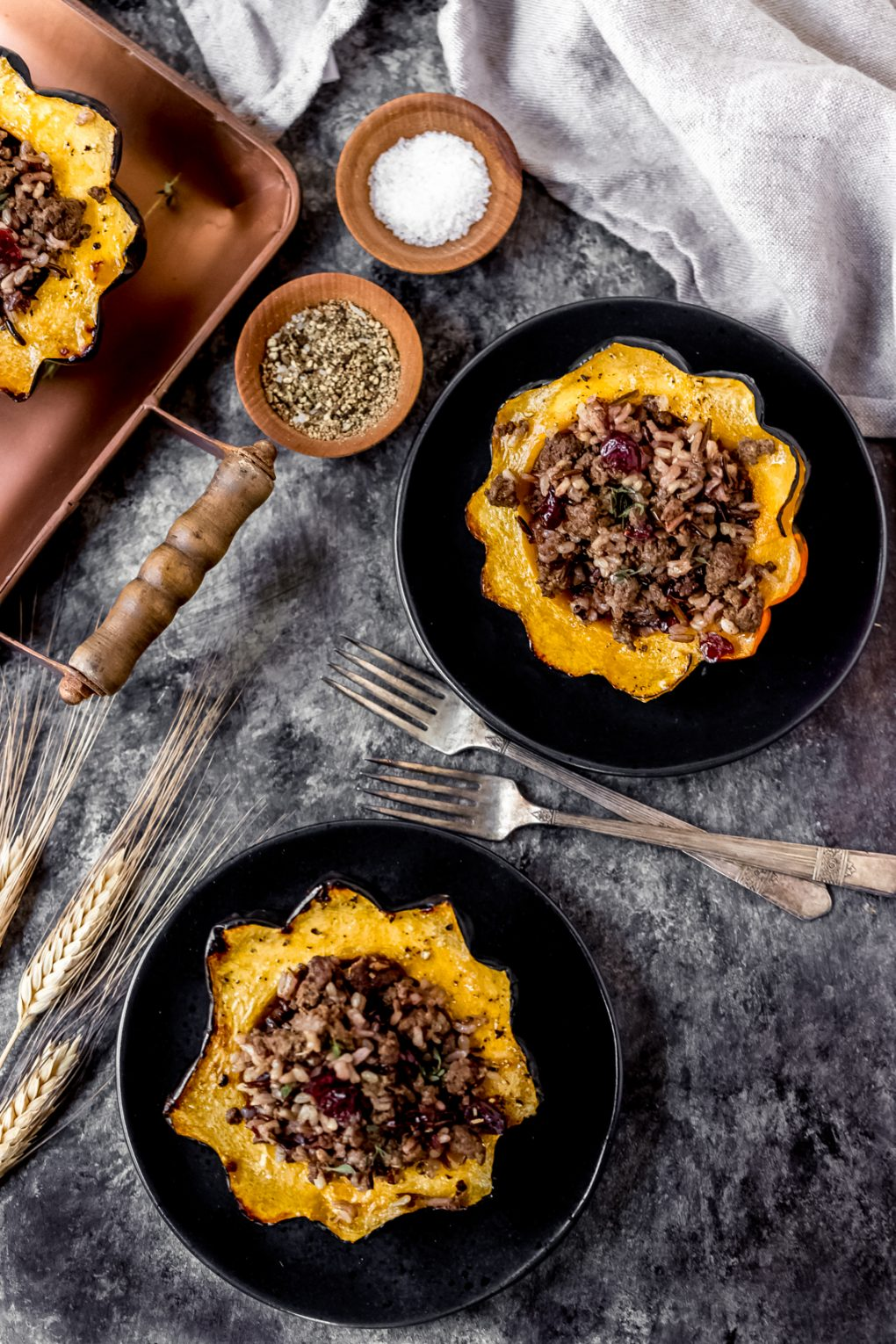 two ground elk stuffed acorn squash on plates