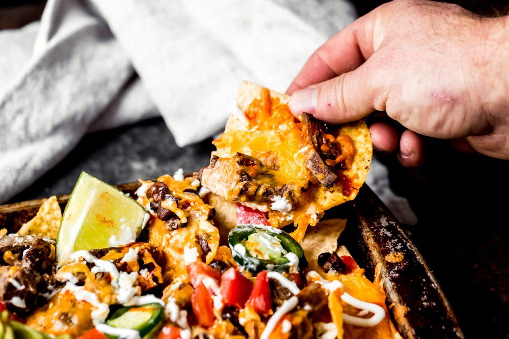 a man grabbing a chip from sheet pan venison steak nachos