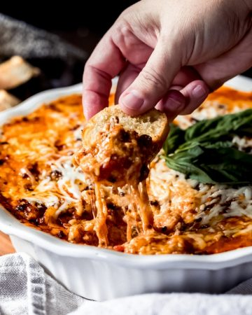 a person dipping bread into a bowl of ground venison lasagna dip