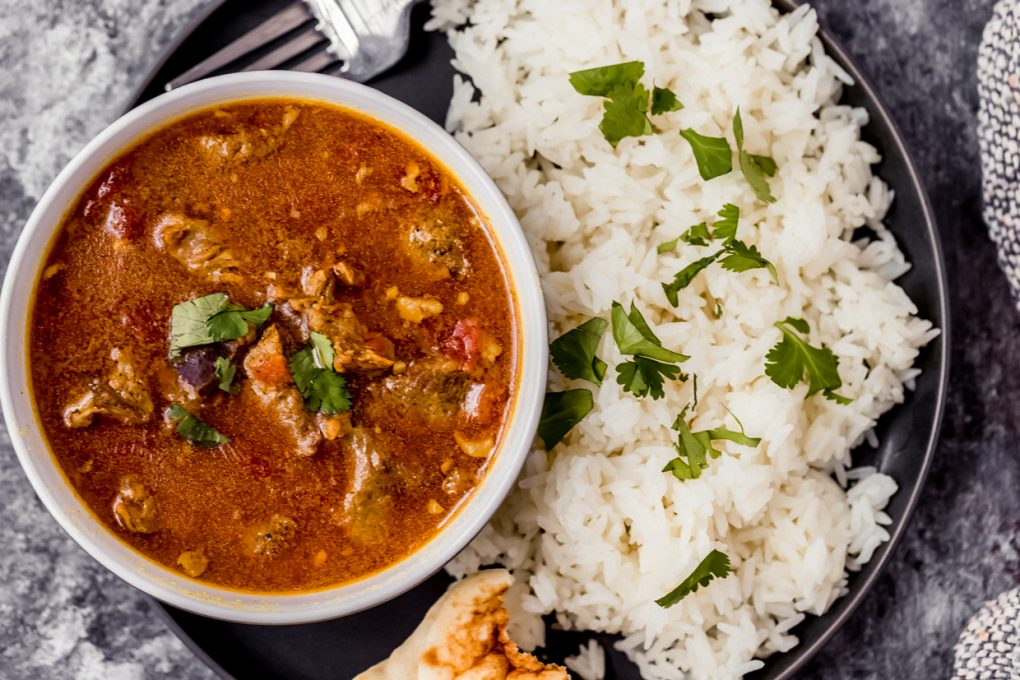 a bowl of instant pot venison curry with a side of rice