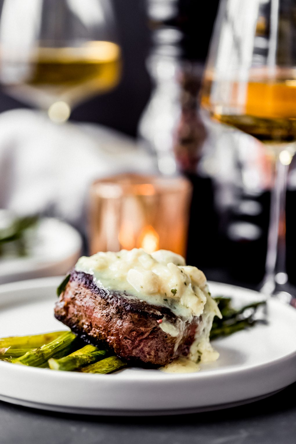 bison filet mignon Oscar on a plate with asparagus