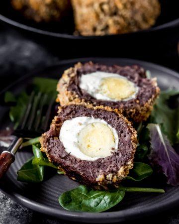 a venison scotch eggs on a plate cut in half